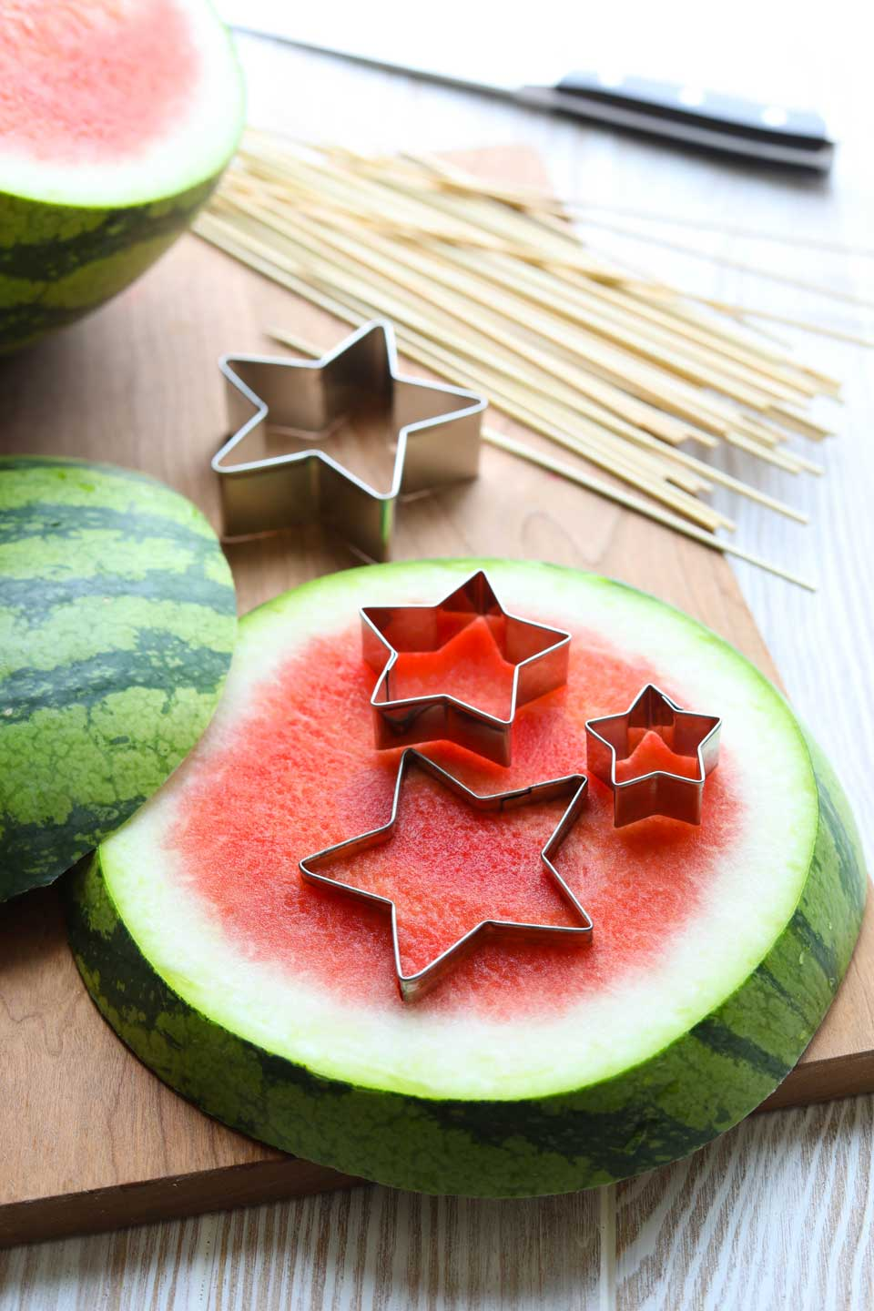 Slices of watermelon on a cutting board, with star cookie cutters and skewers to make fruit kabobs