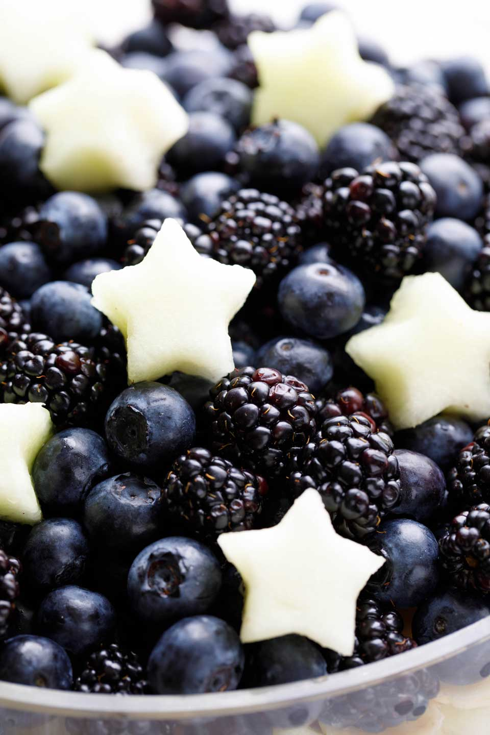 Closeup of blueberries and blackberries, topped with little white stars cut out of a honeydew melon