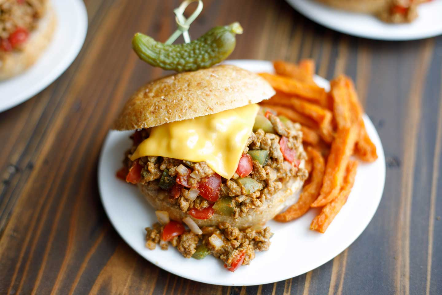 A sweet pickle on top and sweet potato fries to the side - perfect companions for these Cheeseburger Sloppy Joes!