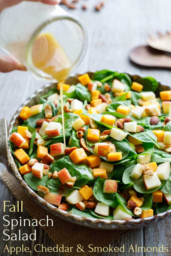 Juicy apples, sharp cheddar and smoky almonds are perfect toppers for this fantastic fall salad recipe! Drizzle with our low-fat cider vinaigrette for an easy 10-minute salad everyone will love! You can even switch it up with romaine instead of spinach. Make our Spinach Salad with Apple, Cheddar and Smoked Almonds on busy weeknights, or for easy entertaining! | spinach recipes | spinach salad recipes | spinach salad dressing | fall salads | #spinach #salad #apples | www.TwoHealthyKitchens.com