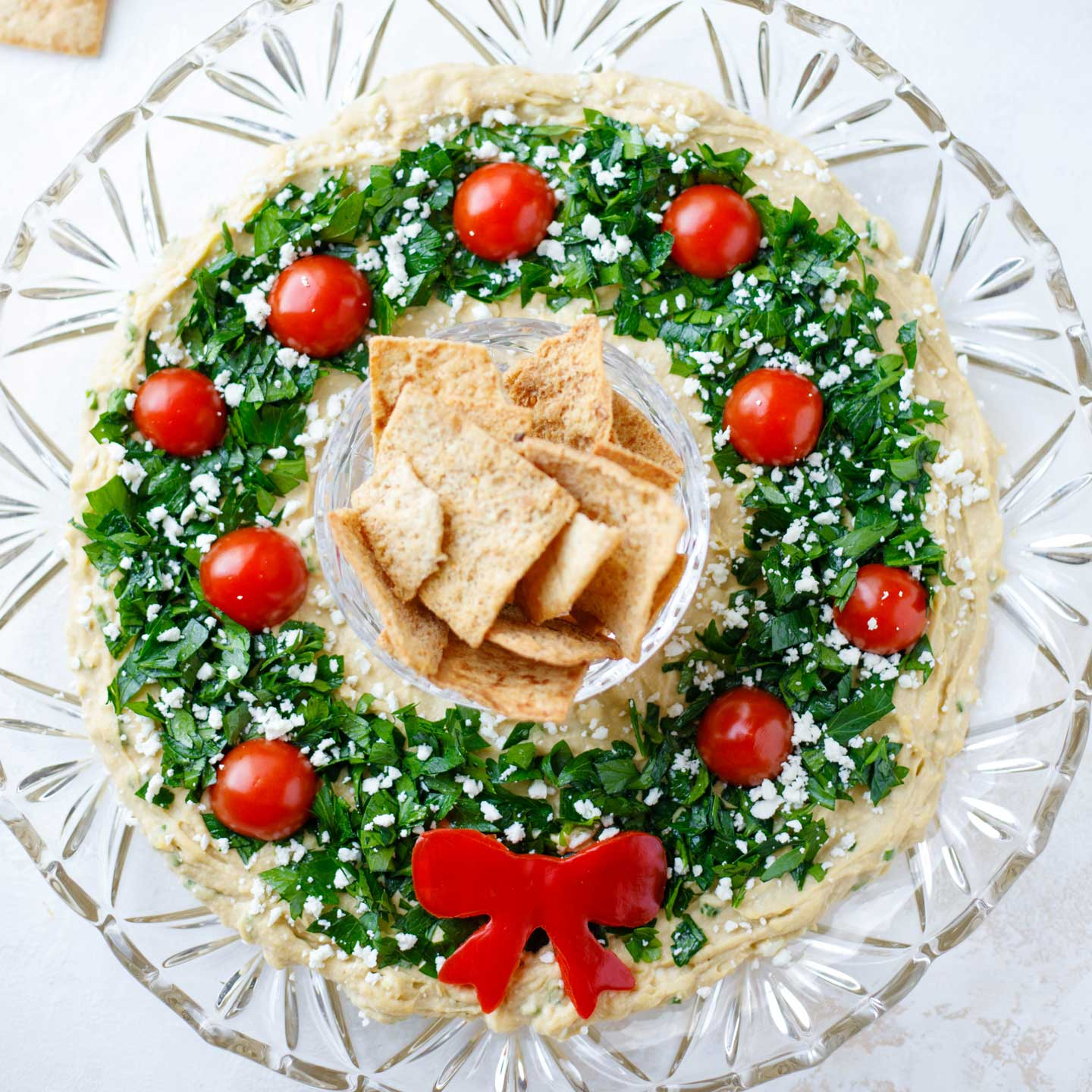 "A super-easy showstopper! This ""Hummus Wreath"" Christmas appetizer recipe is quick and simple, but so pretty and impressive! Even better? You can make it ENTIRELY AHEAD (just perfect during the hectic holiday season)! Terrific served with pita chips or pretty veggies. It's a huge hit every time we serve it! Try it today and see for yourself – you'll love all the impressed ooooohs and aaaaahs you'll hear! 