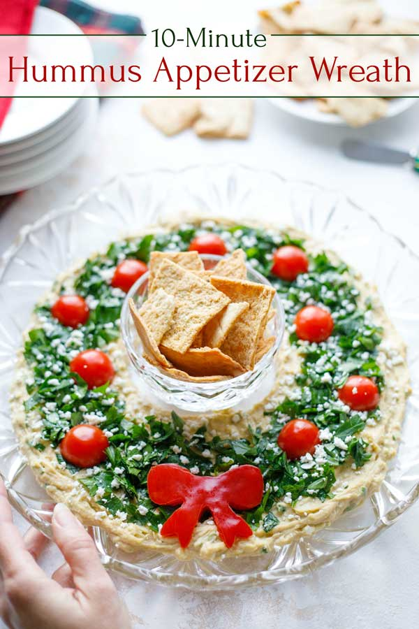 "So impressive, but SO EASY! You'll wow 'em with this gorgeous appetizer dip … but you won't have to stress out to make it! Our ""Hummus Wreath"" Christmas appetizer recipe comes together in minutes! And, you can even make it ENTIRELY AHEAD – total lifesaver during the hectic holidays! Loaded with big flavor, but also terrific nutrition (no guilt here!). This wins raves every time – try it yourself and bask in the compliments! 
