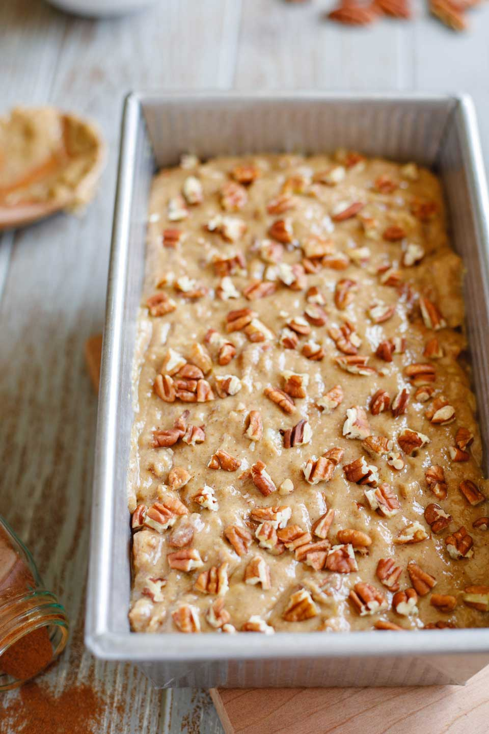 Loaf pan full of batter, sprinkled with pieces of pecans and ready for baking