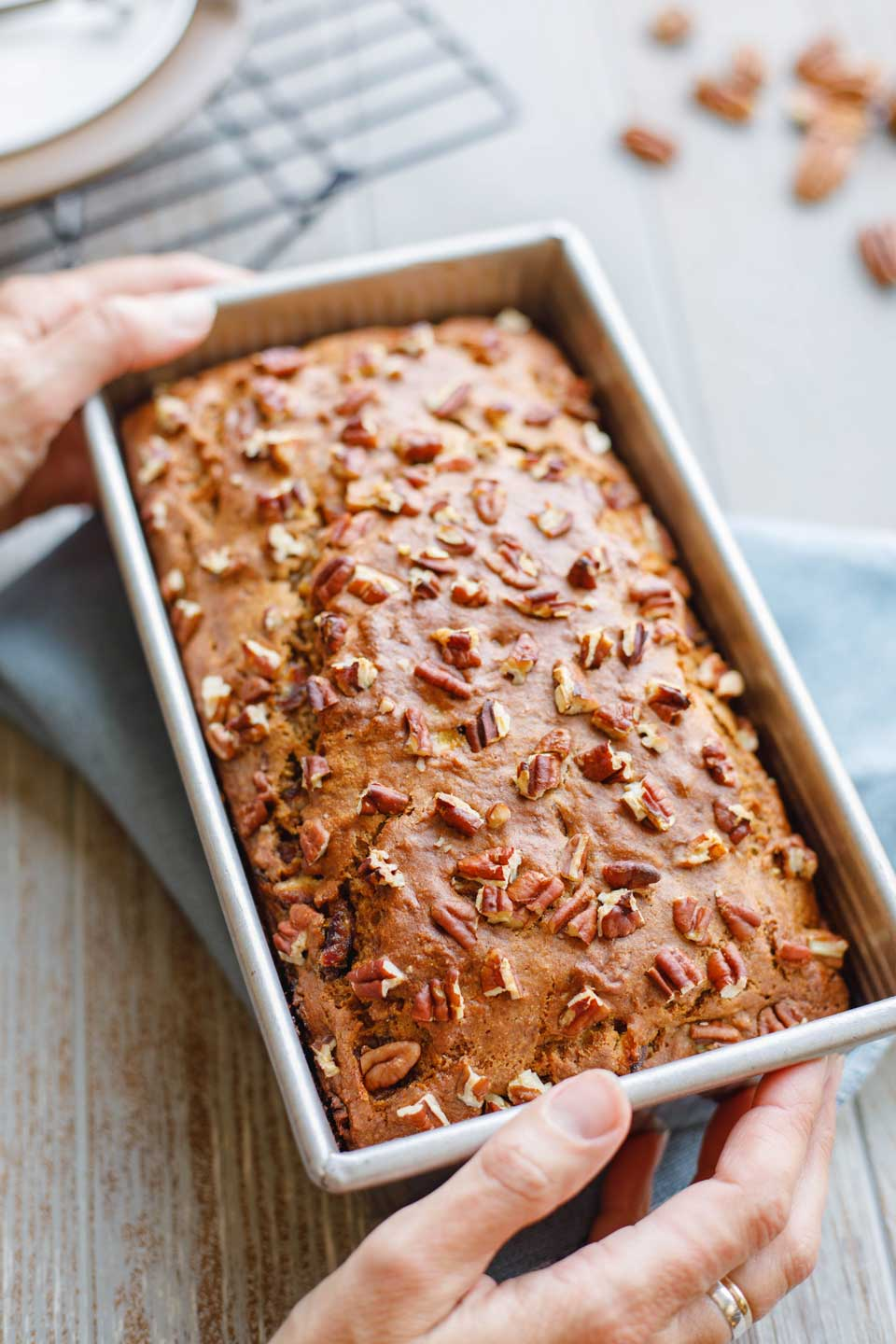 Final baked loaf pan of this Healthy Whole Wheat Banana Bread recipe, being held by two hands, resting on a blue cloth