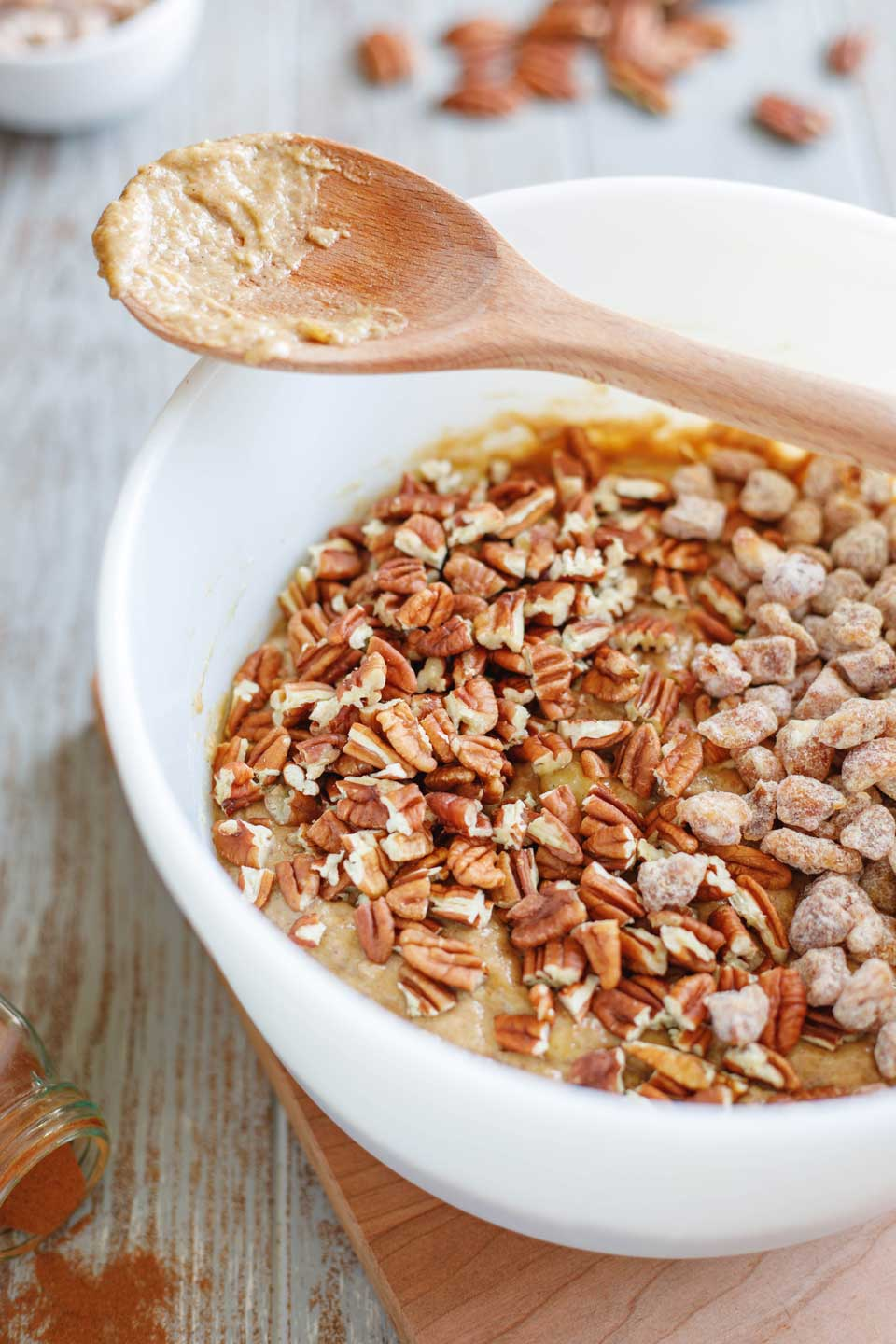 Mixing bowl full of banana bread batter with dates and pecans sprinkled on top, ready to be mixed in with a wooden spoon