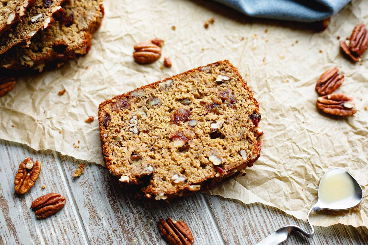 slice of this healthy banana bread on parchment, surrounded by honey spoon, pecans, and additional slices of bread