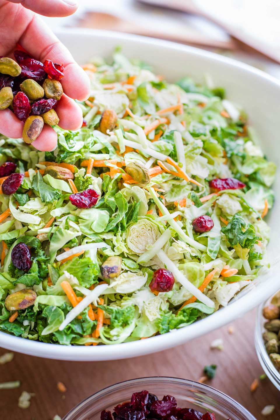 hand sprinkling dried cranberries and pistachios on top of shaved Brussels sprouts in a large bowl