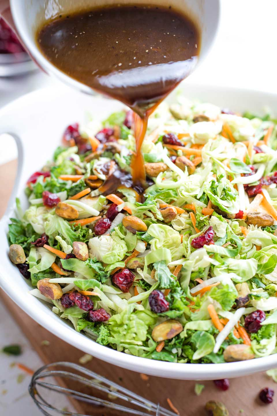 Dish of Maple-Balsamic Salad Dressing being poured on top of a large bowl of the Brussel Sprout Salad