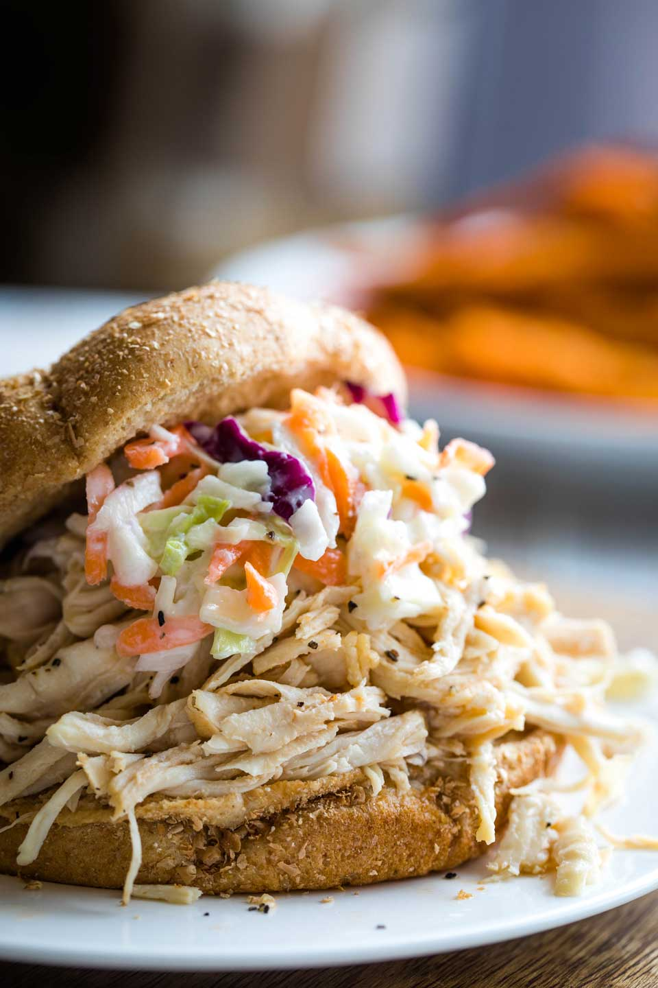 closeup of a pulled chicken sandwich, topped with coleslaw