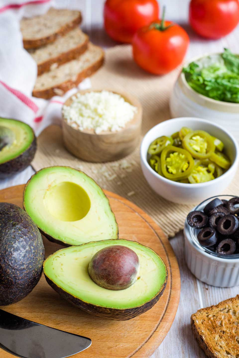 ingredients for Mexican Avocado Toast - an avocado cut open, bowls of olives and jalapenos and lettuce and cheese, slices of bread, and tomatoes