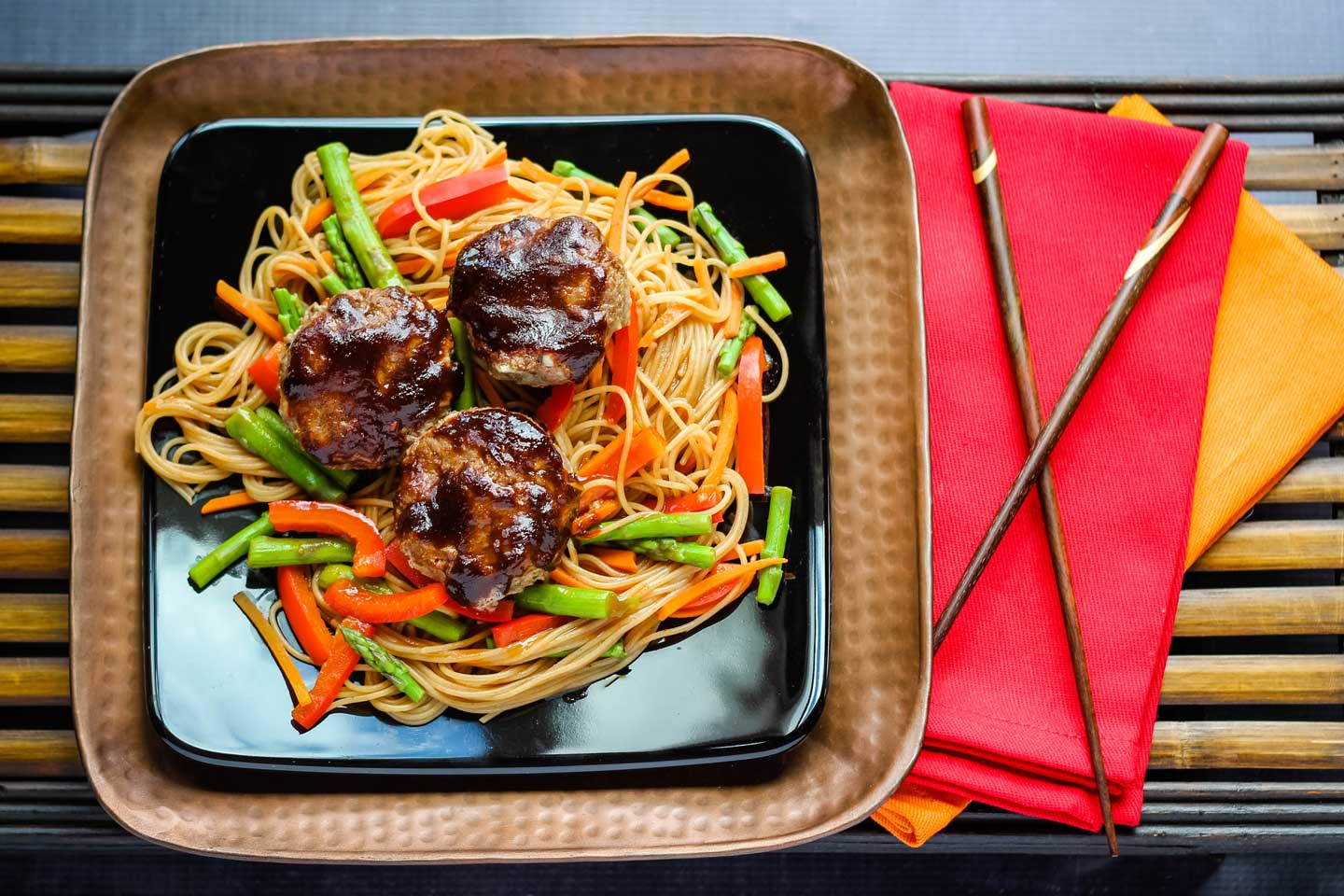 example of a healthy hamburger meat recipe - mini Asian Meatloaves plated on top of vegetables and noodles, next to napkins and chopsticks