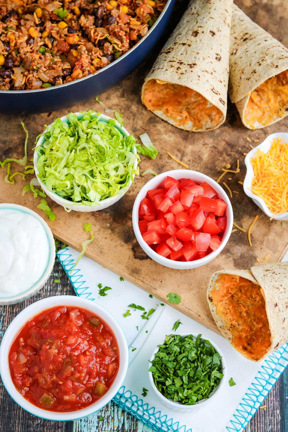 healthy toppings next to tortillas and pan of Mexican healthy ground beef recipe