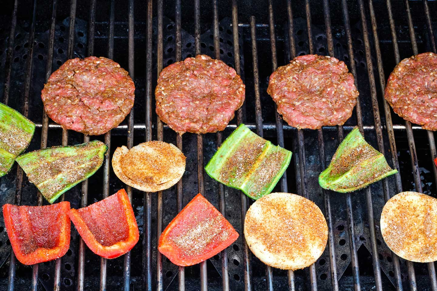 four hamburgers plus seasoned peppers and onions, cooking on outdoor grill