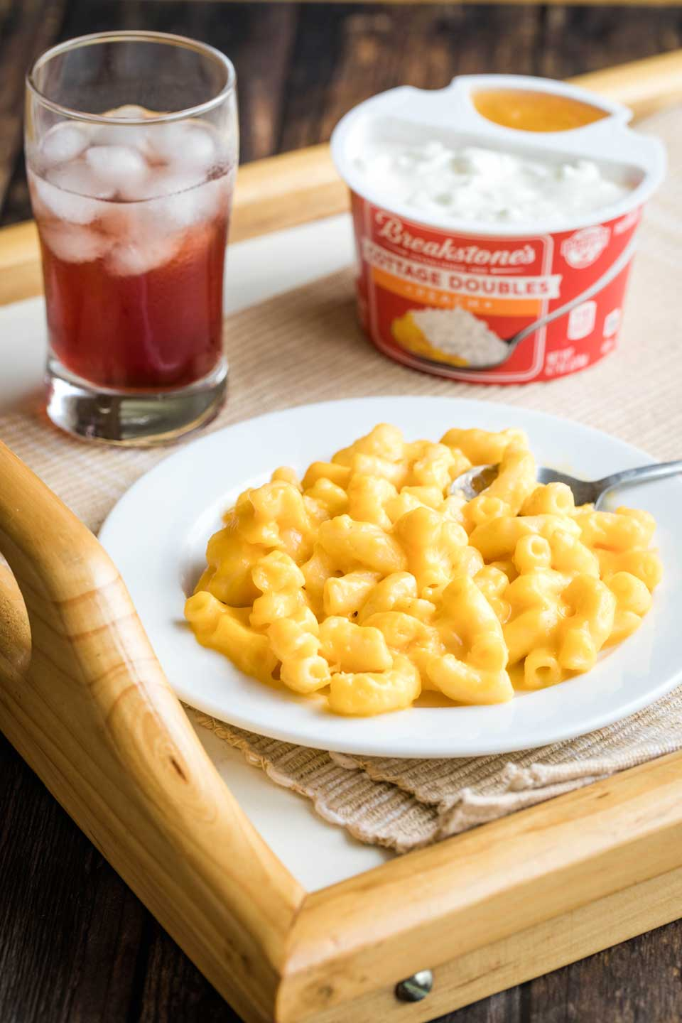 tray holding a plate of mac and cheese, a glass of juice, and a container of cottage cheese