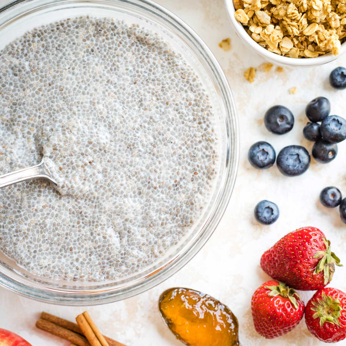 Large bowl of basic Chia Pudding, surrounded by mix-ins like fruit, granola and cinnamon