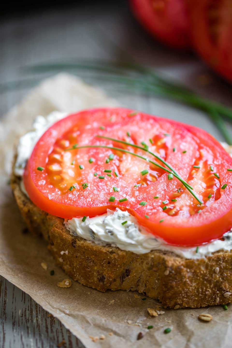 closeup of one tomato sandwich with cream cheese and chives