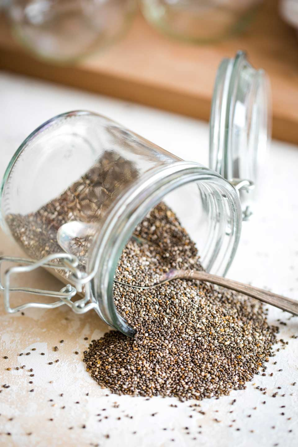 Jar of chia seeds, dumped over sideways with seeds spilling out