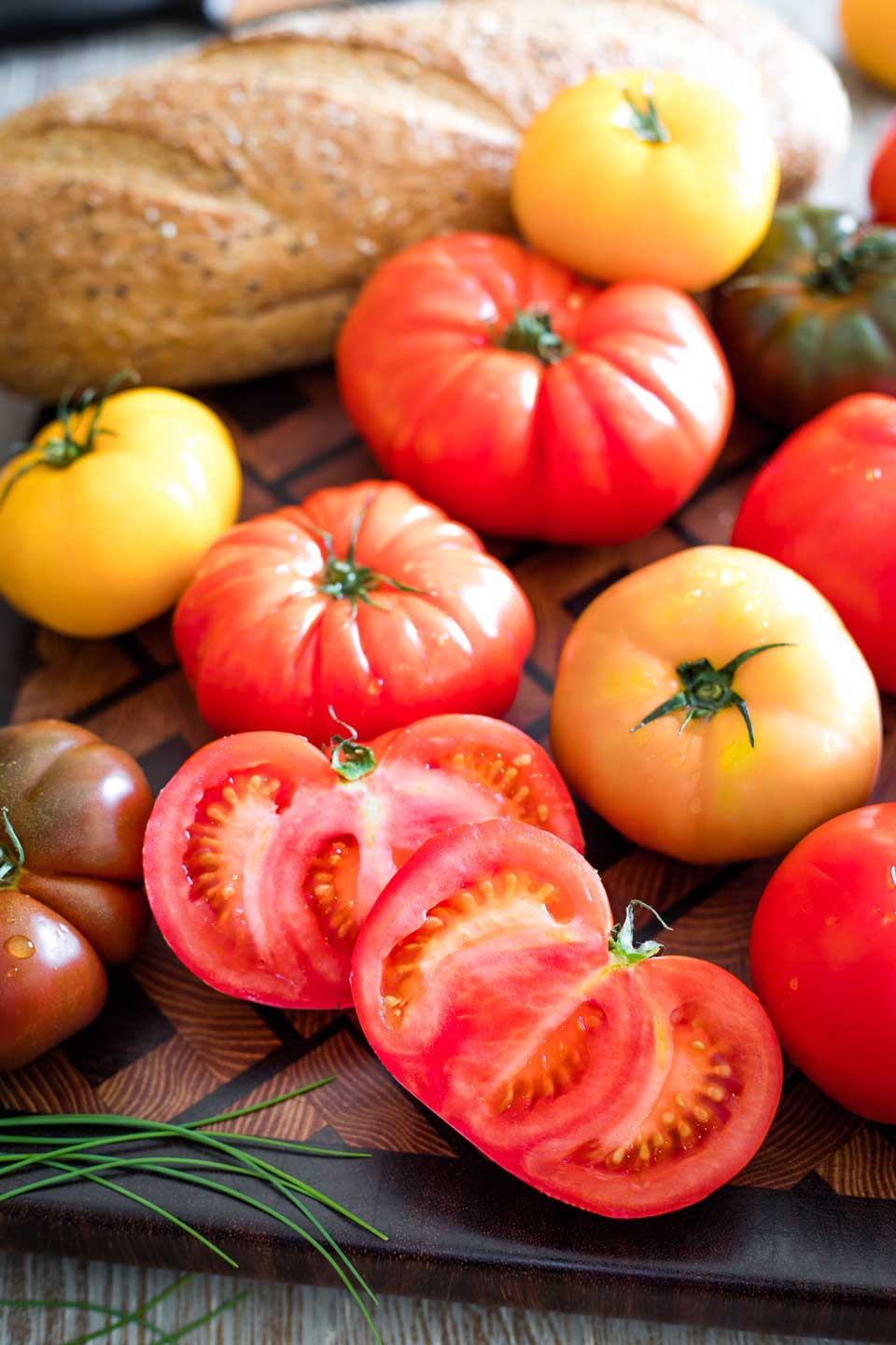 Different colors of tomatoes with one cut open, plus a grainy loaf of bread in background