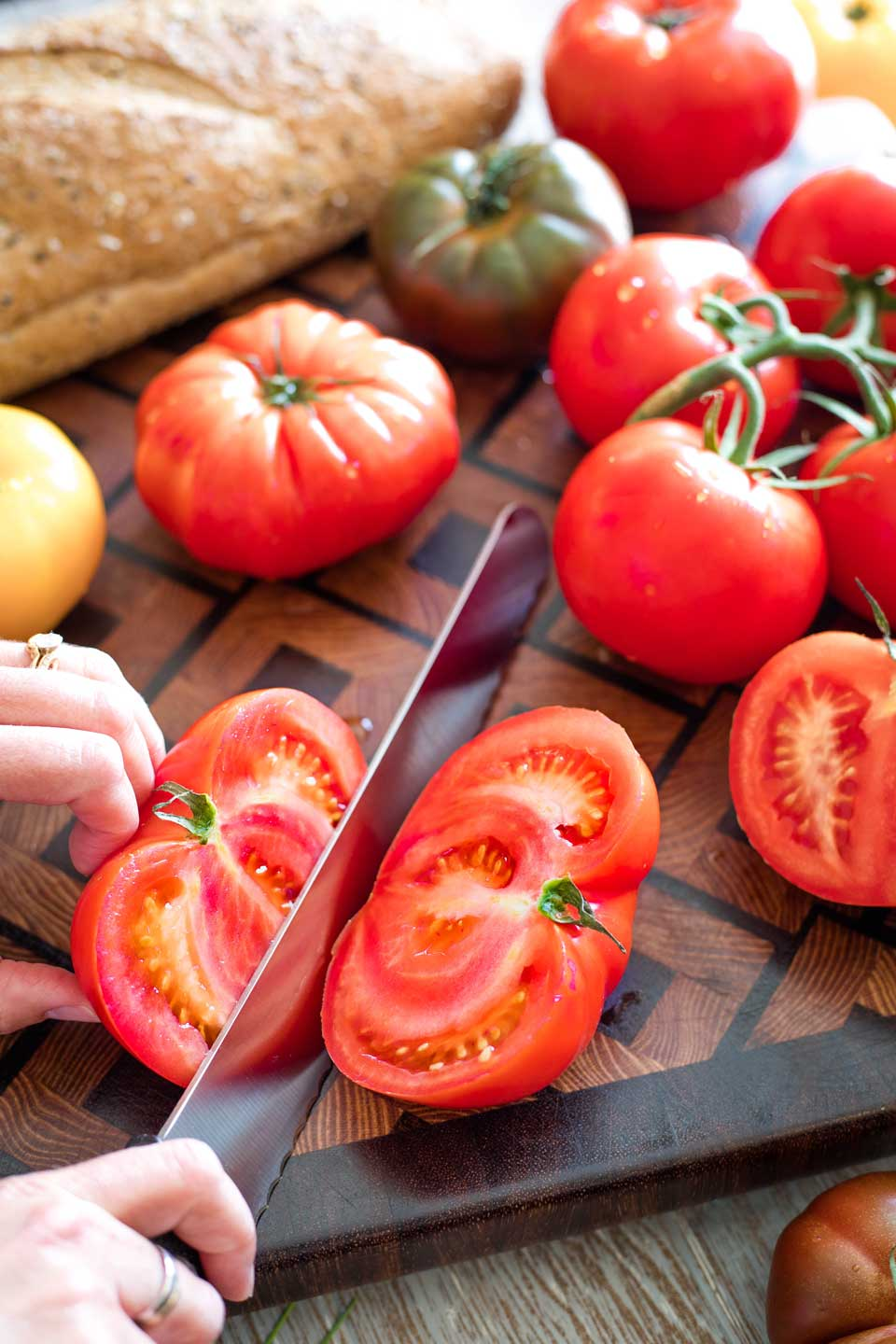 serrated knife slicing through tomato on cutting board, surrounded by other tomatoes