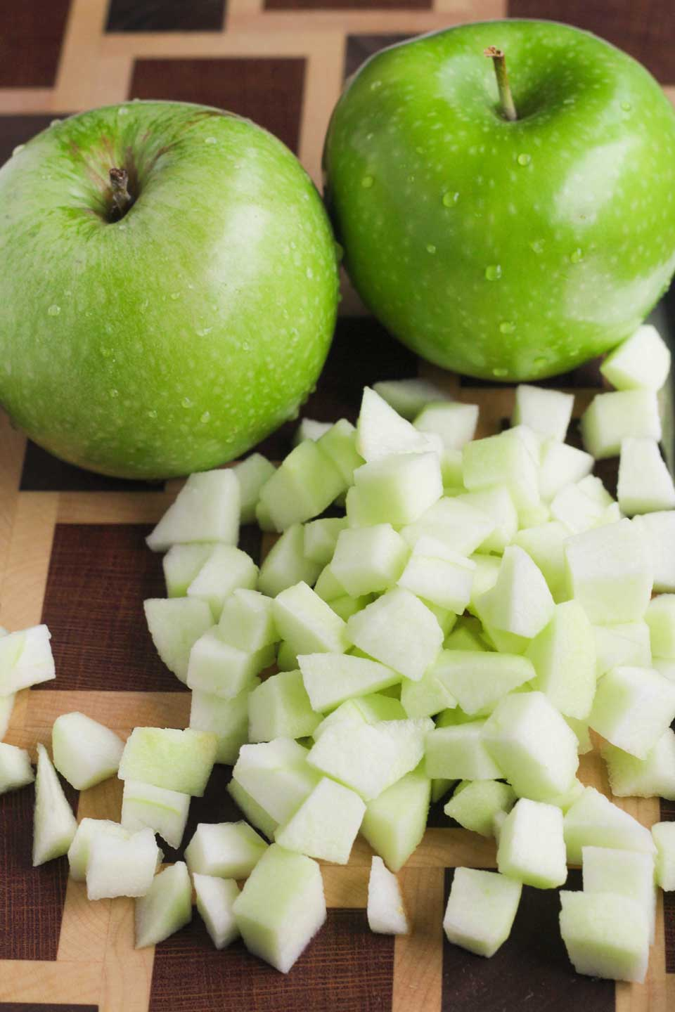 two green apples on cutting board with pile of diced apples ready for apple recipes