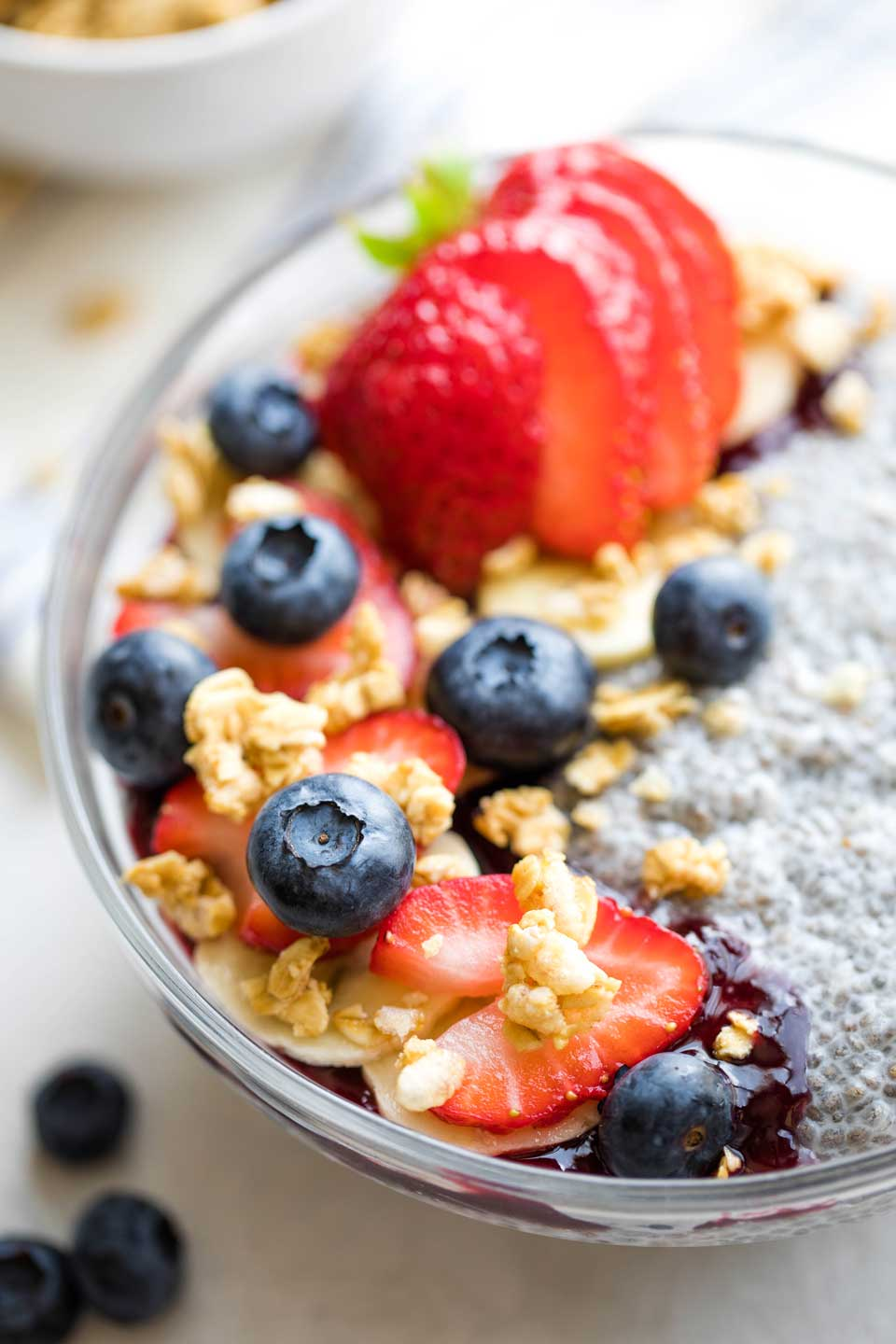 closeup photo of the toppings on a bowl of chia pudding - strawberries, blueberries, sliced bananas, jelly and granola