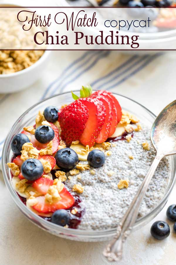 coconut milk chia pudding in serving bowl, topped with berries, granola and blackberry jelly, with spoon laying on top