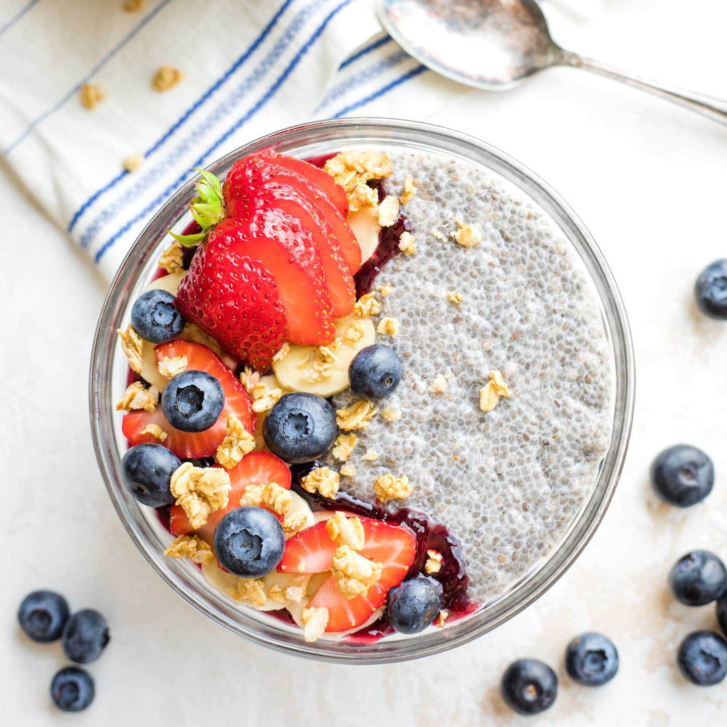 bowl of Coconut Milk Chia Pudding topped with berries and granola with spoon in background