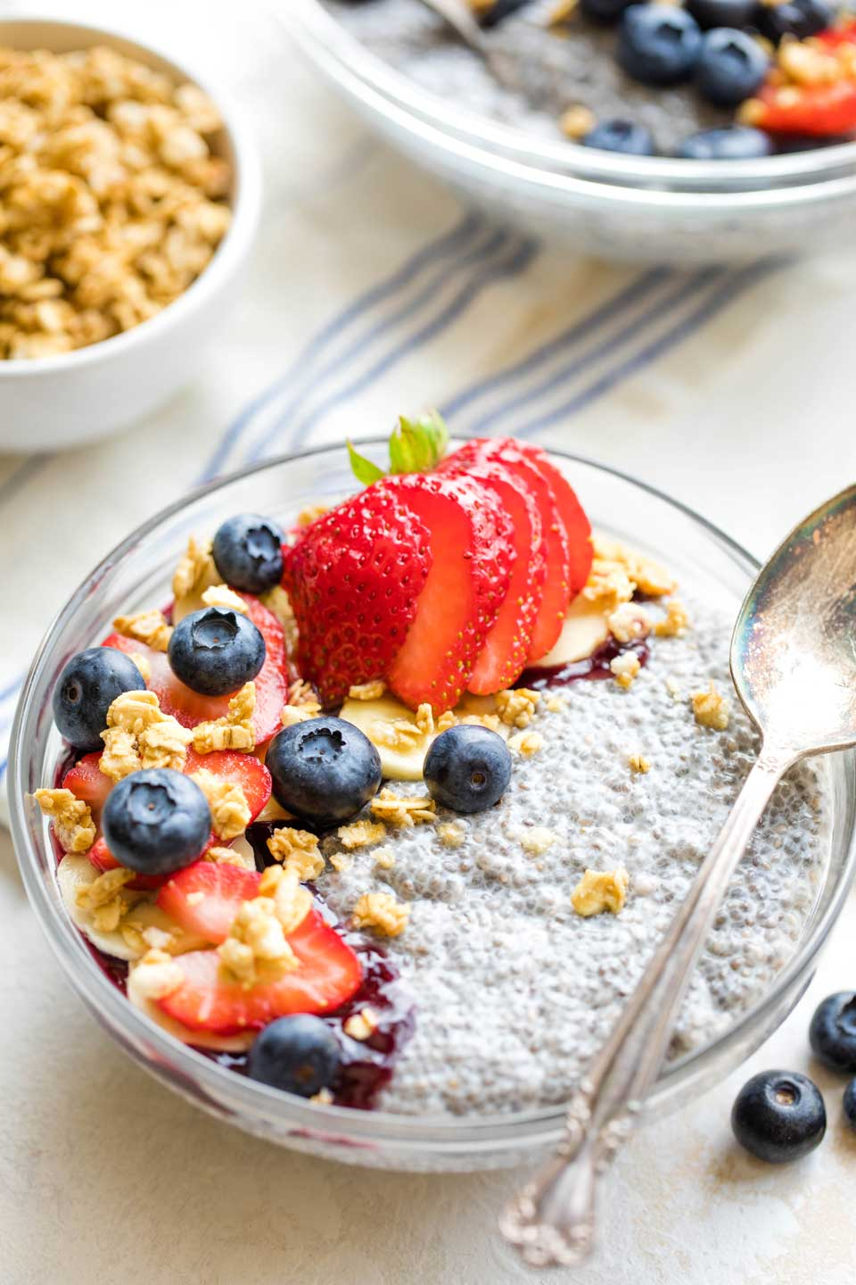 bowl of chia seed pudding with topping, a spoon laying across the bowl, and the serving bowl and extra toppings in background