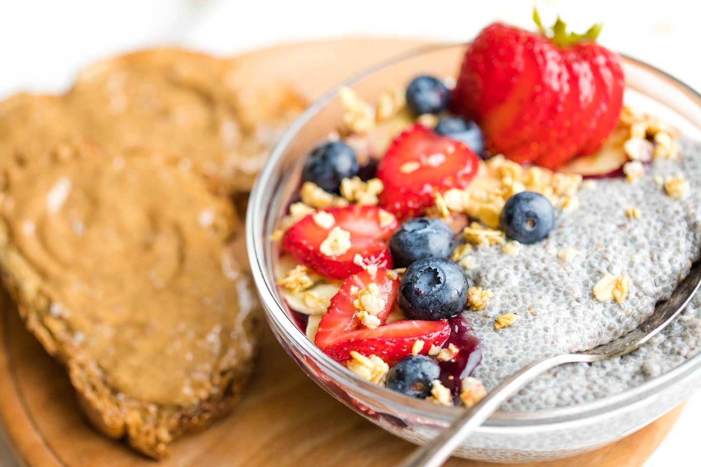 serving bowl of chia pudding with fruit, surrounded by toast topped with almond butter