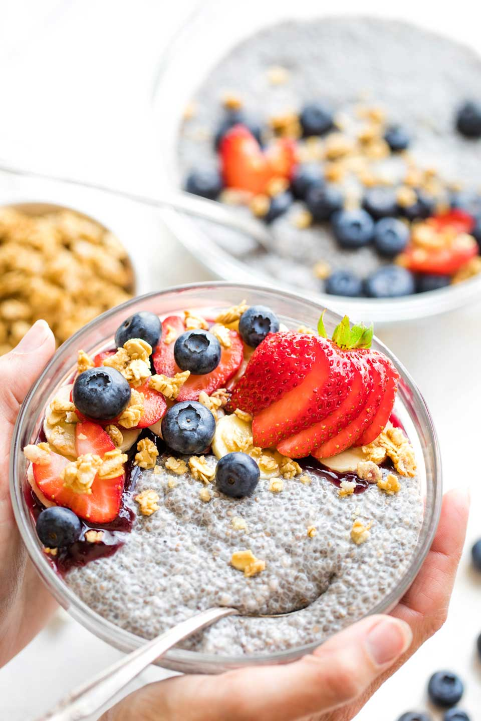 hands holding bowl of breakfast chia pudding, with serving bowl in background