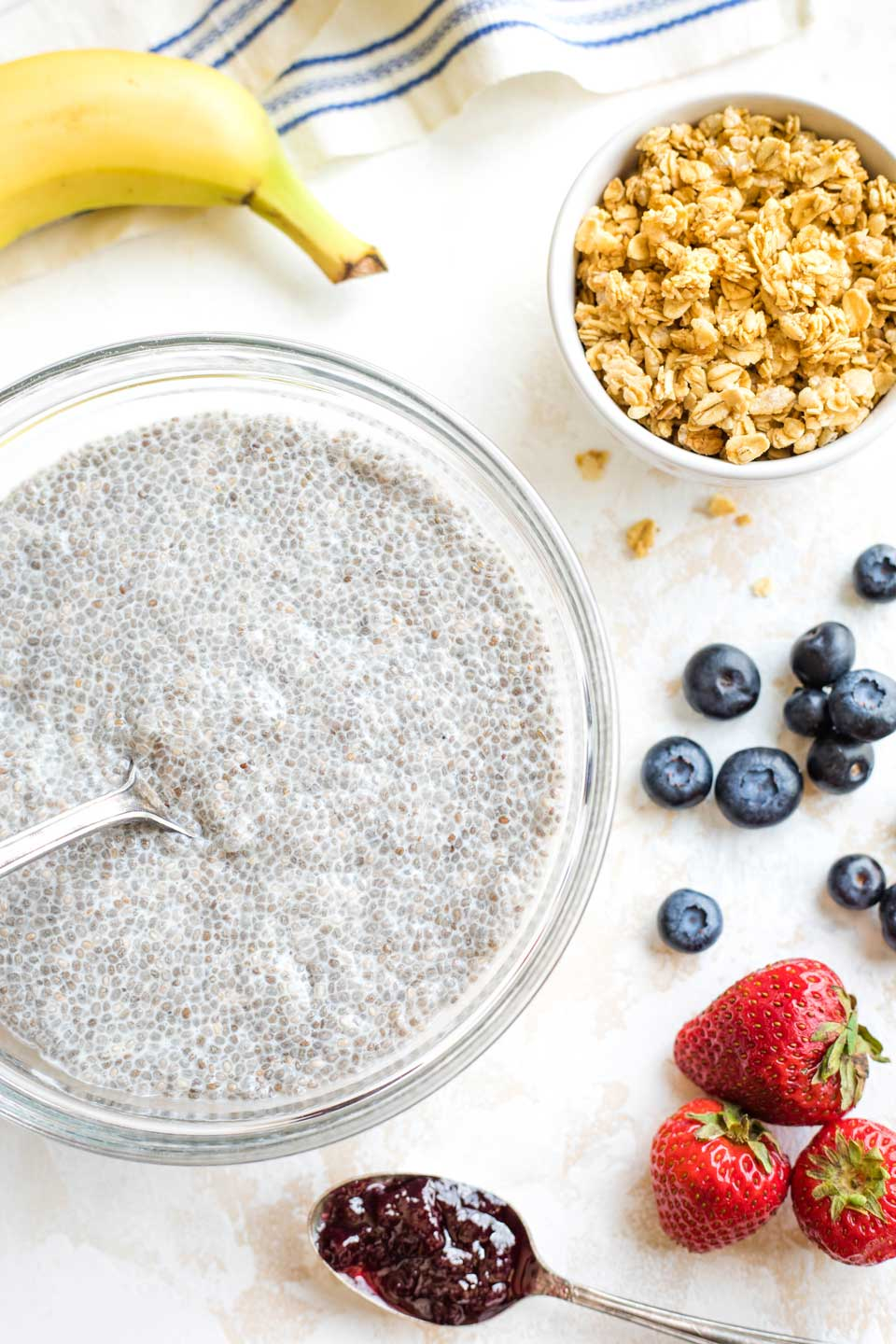 serving bowl with finished chia pudding, surrounded by toppings like fruits, granola and jelly