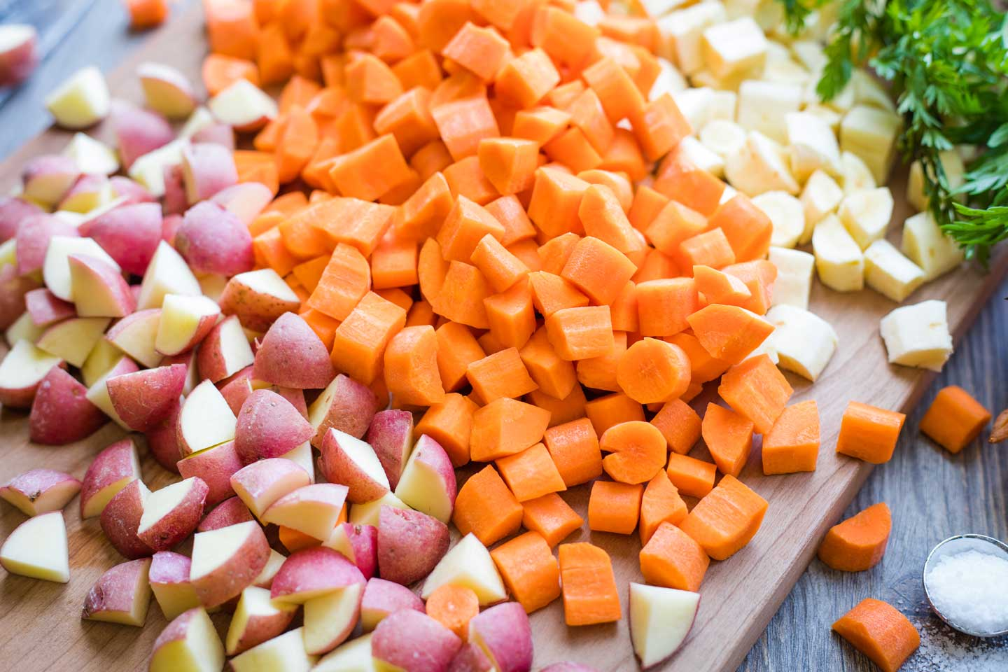 """piles of 1/2""""-diced red potatoes, carrots, and parsnips on cutting board"""
