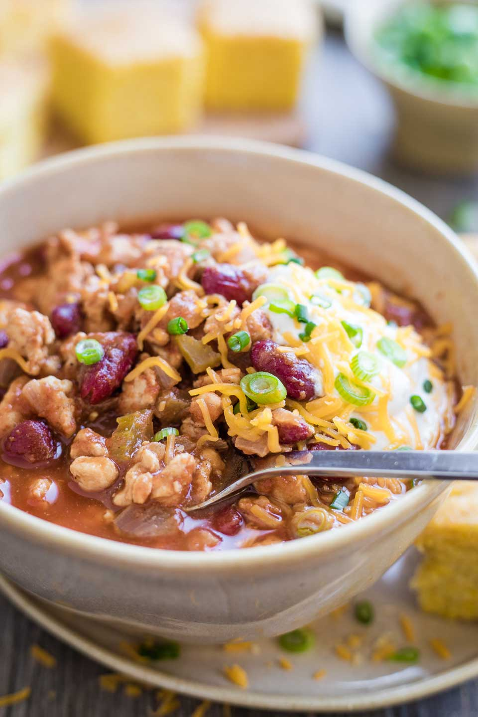 bowl of turkey chili with toppings, served next to wedge of corn bread for dinner