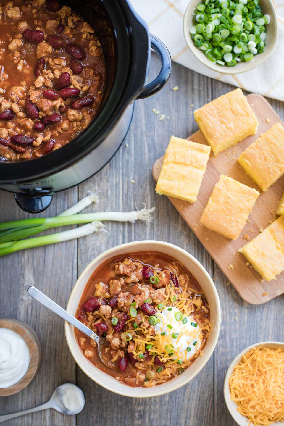 overhead of bowl full of chili, with crockpot in background, surrounded by corn bread and toppings