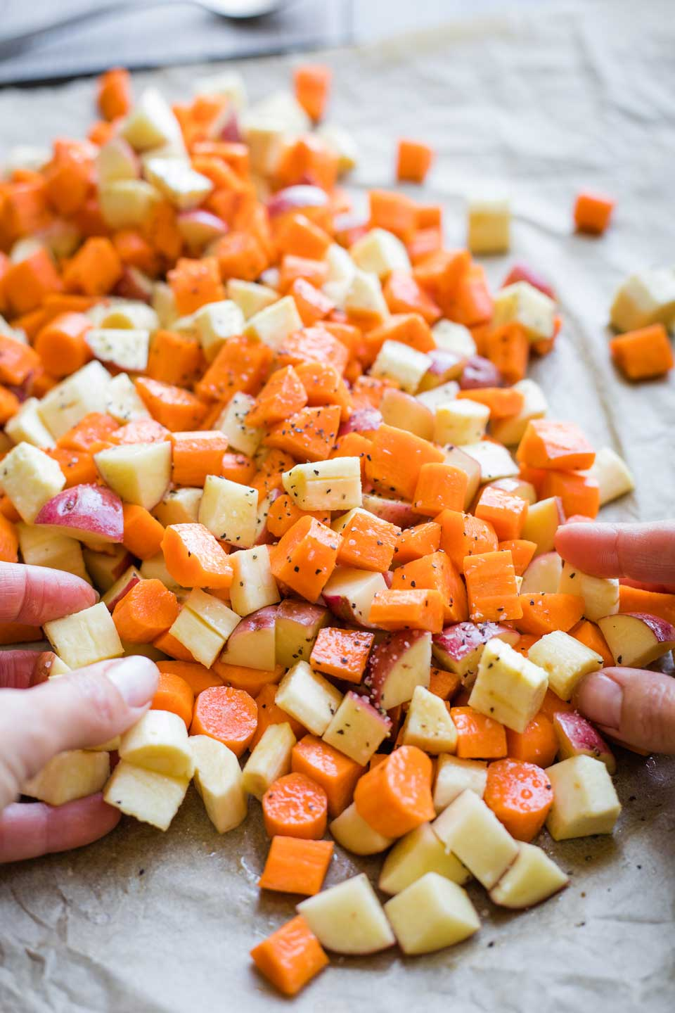 hands tossing diced root vegetables on sheet pan with oil, salt, and pepper