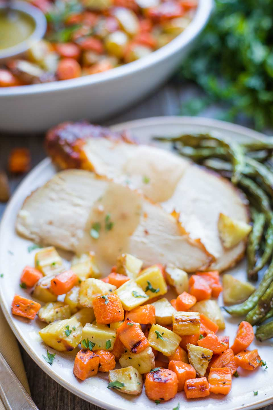 Roasted carrots, potatoes and parsnips piled on dinner plate next to turkey and gravy, and roasted green beans