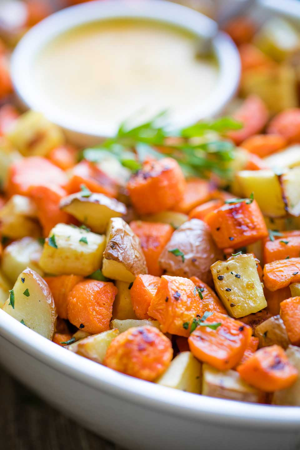 closeup of roasted veggies in serving bowl, with a bowl of dressing tucked into the bowl at the back