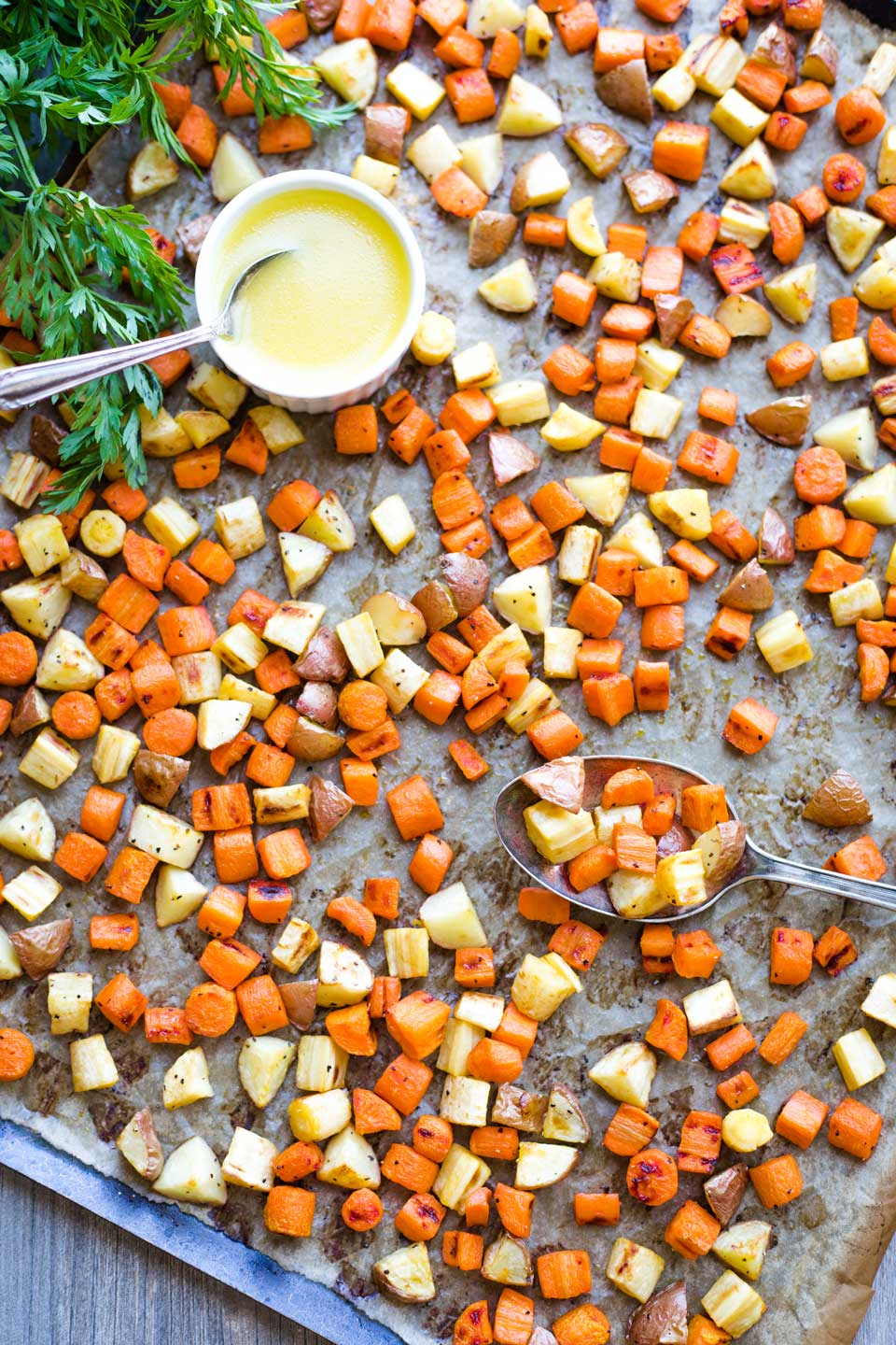 overhead of sheet pan with roasted veggies, a serving spoon, and a small bowl of drizzle