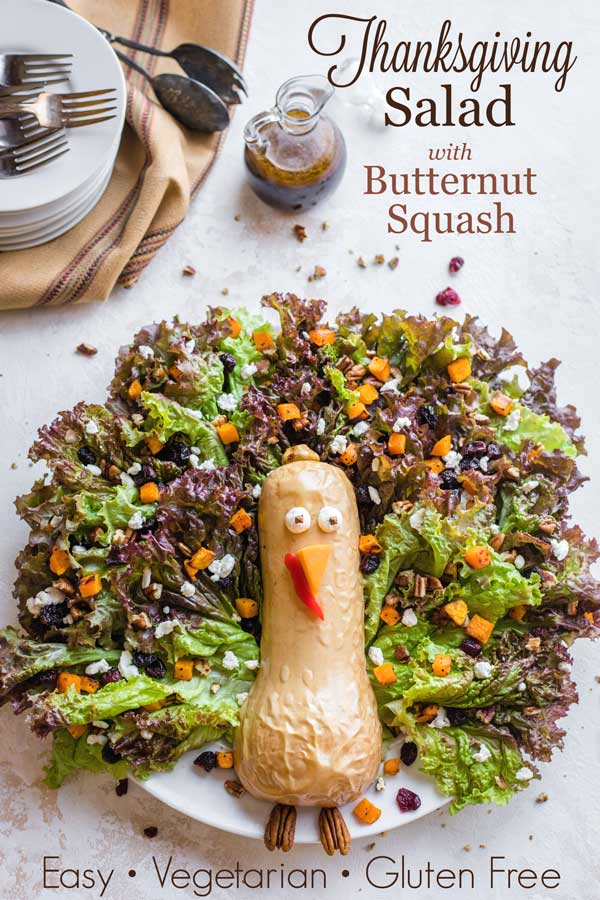 """overhead view of finished salad nest to dressing cruet and serving plates - with text overlay reading """"Thanksgiving Salad with Butternut Squash"""""""