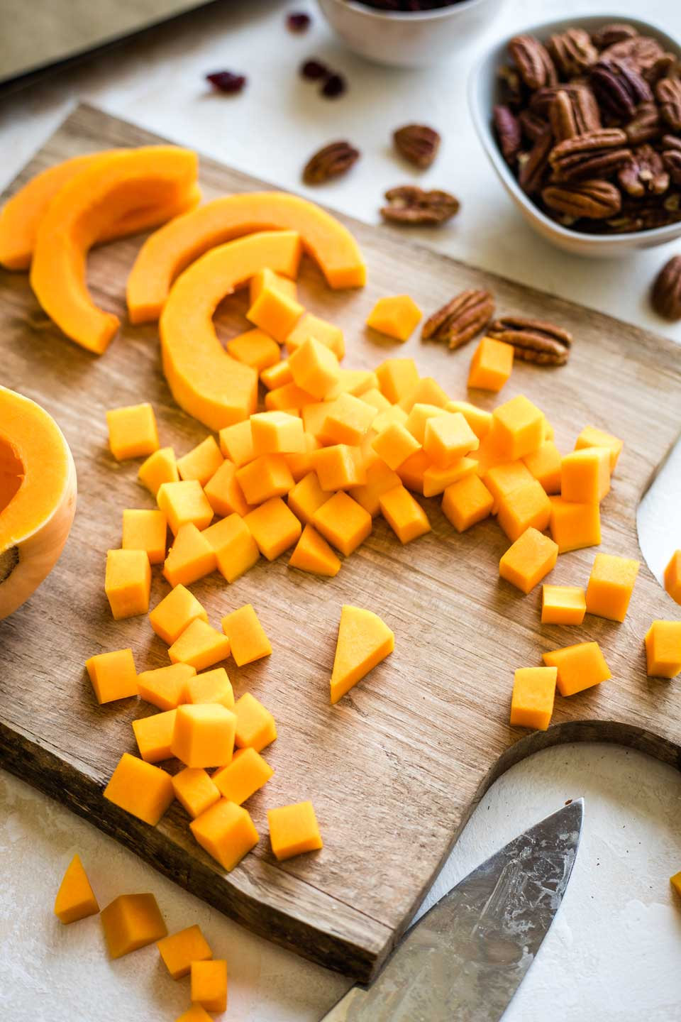 butternut squash being cut and chopped on cutting board, with one triangular piece prominently at middle of cutting board