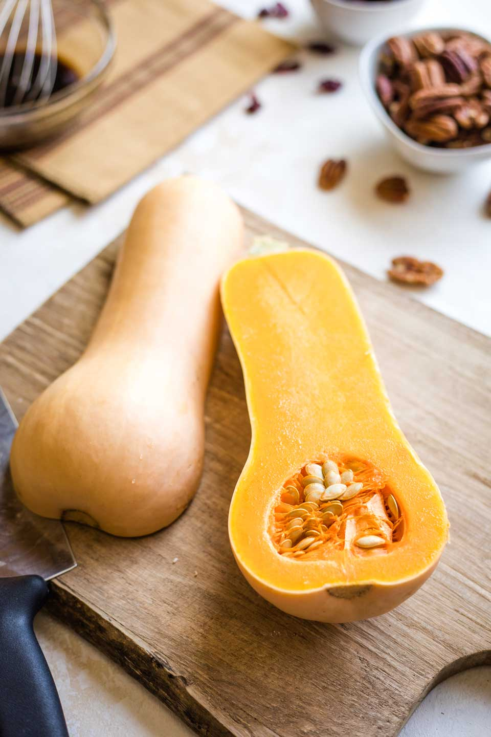 butternut squash on cutting board, cut open vertically from stem to bottom