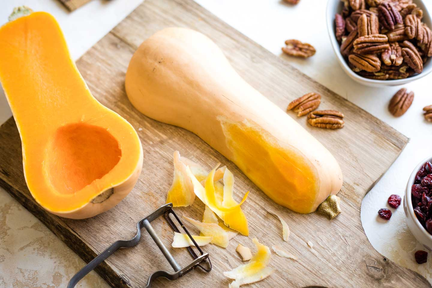 butternut squash halves on cutting board with seeds removed and one starting to be peeled with vegetable peeler