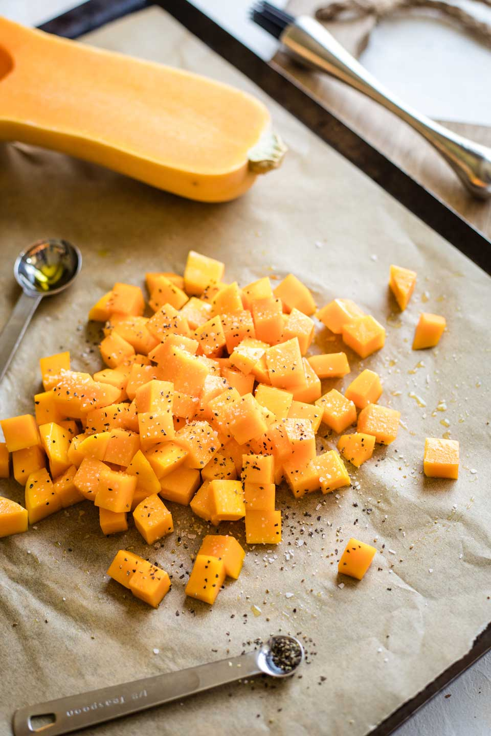 cubed squash piled on parchment-lined baking sheet, being tossed with olive oil, salt, and pepper