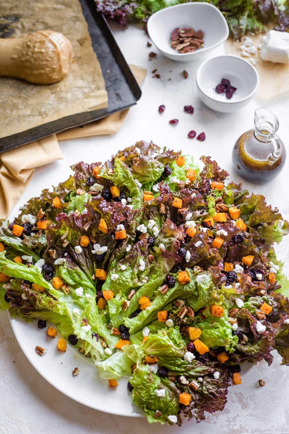 overhead of salad platter with lettuce leaves layered on, sprinkled with toppings