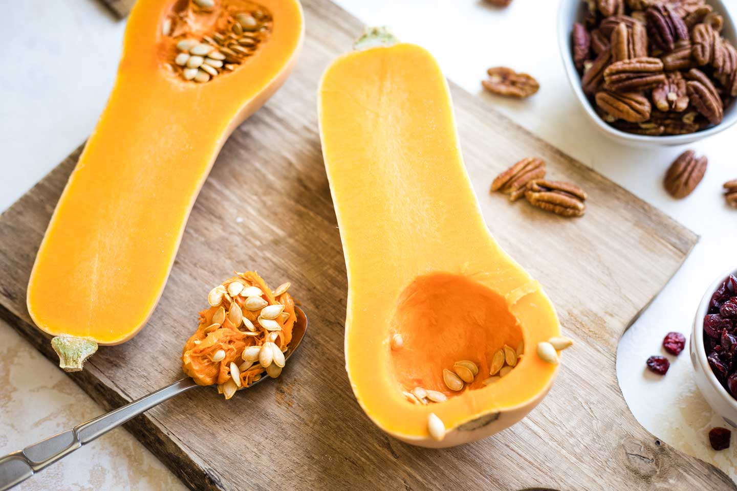 butternut squash on cutting board, with some of the seeds scooped out with a spoon