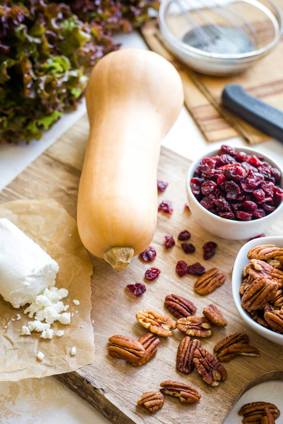 ingredients for Thanksgiving Salad - butternut squash, log of goat cheese, dishes of pecans and cranberries, head of red leaf lettuce