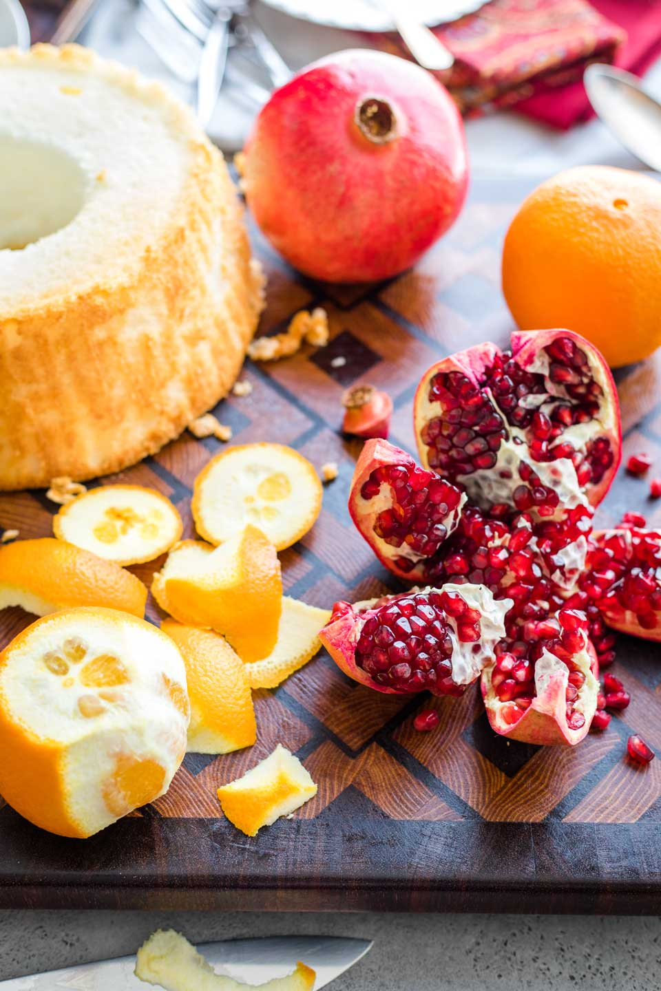 wooden cutting board with a whole angel food cake, and oranges and pomegranates that are beginning to be cut and pulled apart