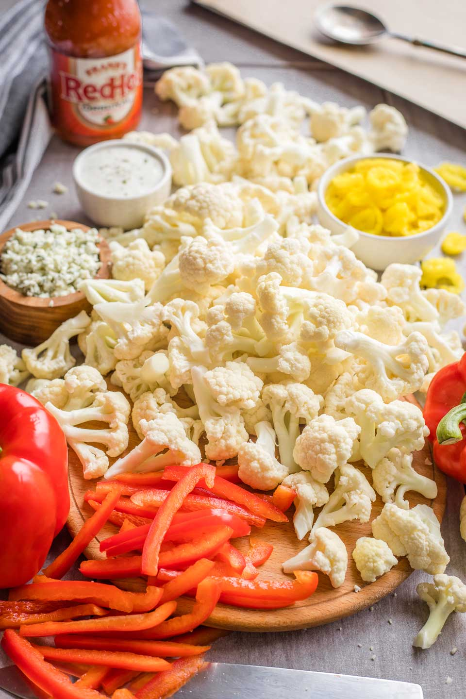 recipe ingredients - cascading pile of cauliflower, slices red peppers, bowls of banana peppers and blue cheese and ranch dressing, bottle of Franks' hot sauce