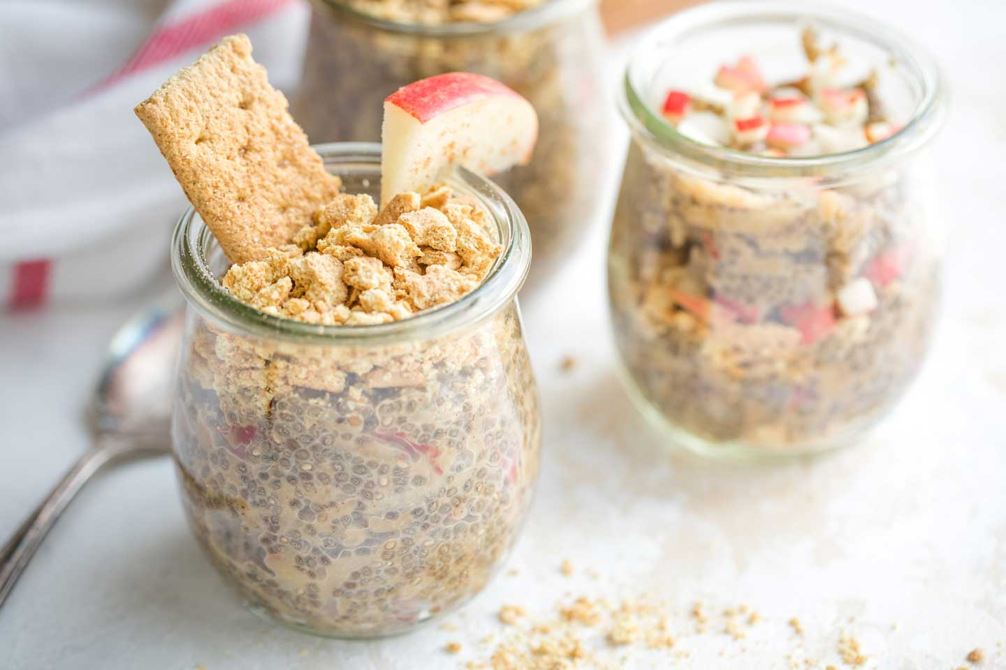 various jars of ready-to-eat, make-ahead chia pudding breakfasts, with a spoon at the ready and a few crumbles of graham cracker nearby