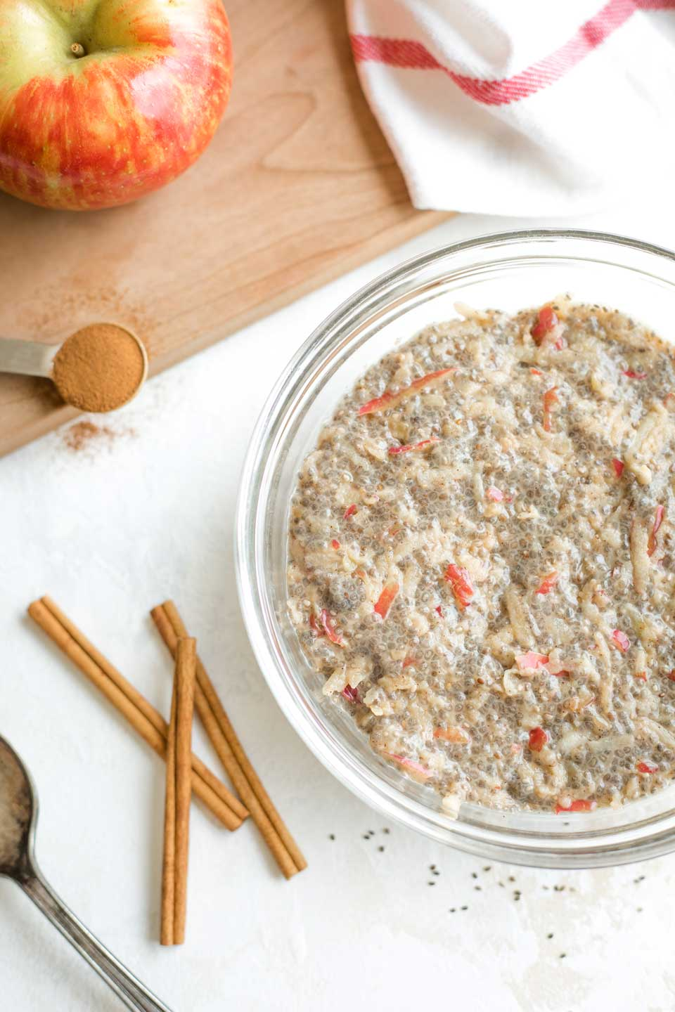 overhead of a bowl filled with this chia pudding recipe, with cinnamon sticks, a red-striped towel, an apple and a serving spoon nearby
